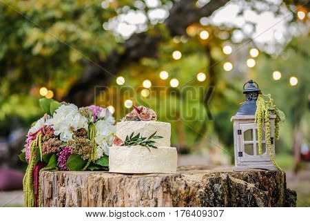 Beautiful wedding decoration with cake bouquet of flowers and a lantern on background of nature