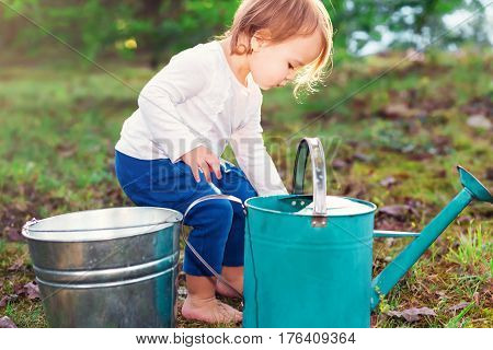 Happy Toddler Girl Playing With Watering Cans