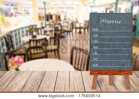 Wooden menu display sign Frame restaurant message board on wooden table Blurred image background Template mock up for adding your design and leave space beside frame for adding more text.