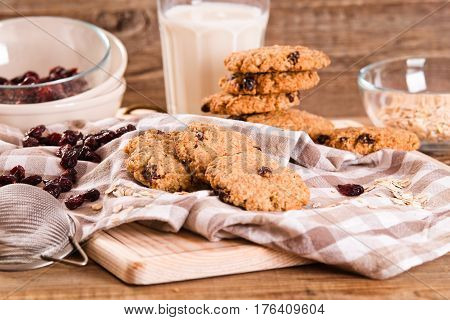 Oatmeal cookies with milk and raisins on cuttingboard.
