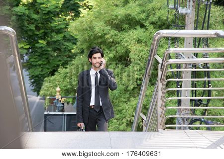 Young handsome bearded businessman walking and talking on smartphone over green city and office building background business technology and people concept. Copy space.