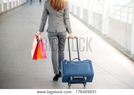 Back of young business girl passenger walking down the walkway with a suitcase at the airport.
