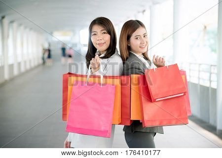 Young business woman smiling and holding shopping bags with purchases. Happy two Asian girl standing on walkway concept for shopping. Focus on hand.