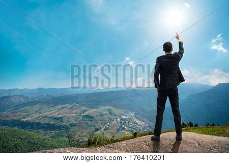 Back of successful businessman pointing up with his finger standing on top of mountain with sunlight sky background. Young man reaching goal success and achievement in his life. Copy space.