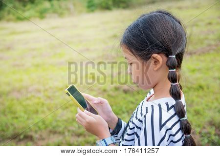 Preteen girl with long black hair standing outdoor with mobile phone in park. Young Asian student reading text messages on cell phone. Kid holding and typing message in smart phone. Copy space.