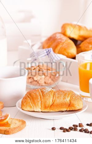 Breakfast with croissants and orange juice on white table.