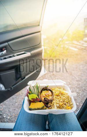 Traditional Organic meal in takeaway cardboard food box on woman lap. Driver stop driving on pavement open the door and having breakfast or lunch.