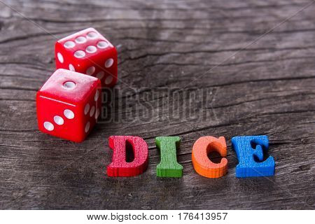 red dice with word dice on the old wooden table, close-up