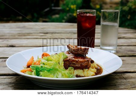Lamb shank with vegetables on an pub outdoor wooden table, drinks next to it