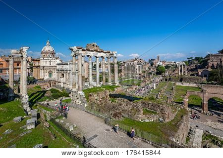 Buildings and ruins, Roman Forum. Rome, Italy - April 20, 2015: Wide angle view of tourists walking at Roman forum in Rome looking at ancient buildings and ruins, Temple of Saturn in the foreground.