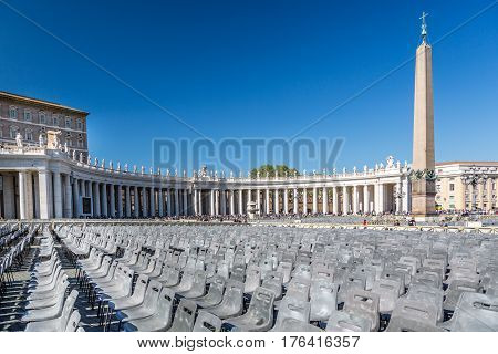 Chairs at St. Peter's Square. St. Peter's Square, Vatican City State - April 21, 2015: Wide angle view of empty chairs at St. Peter´s Square before entrance to public mass, tourists in the background.