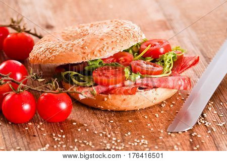 Sesame bagels with pepperoni and cheese on white dish.