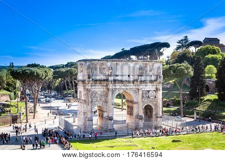 The Arch of Constantine, Rome. Rome, Italy - April 22, 2015: Ancient triumphal arch of Constantin in Rome.  High angle view to show the arch and surrounding square with trees. Tourist around the arch.