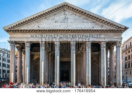 Pantheon In Rome with tourists. Rome, Italy - April 22, 2015: Tourists outside visiting ancient building Pantheon in Rome. Outside, front view wide angle with tourists in lower section of the image.