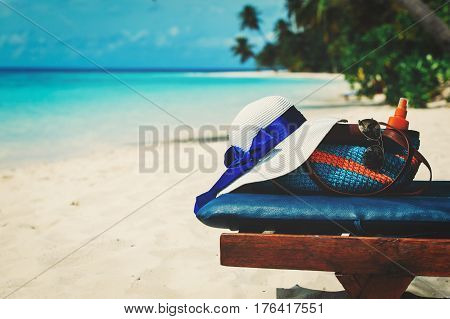 Beach vacation concept - bag, sun glasses and suncream at sea coast