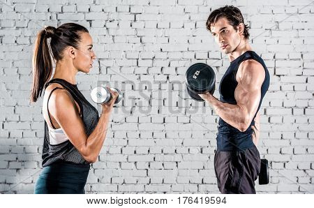 Young sportive man and woman training with dumbbells in gym