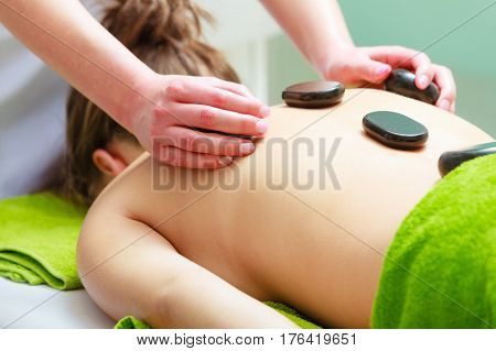 Spa relaxation healthy pleasure concept. Woman lying on stomach having massage with hot rocks stones in beautician