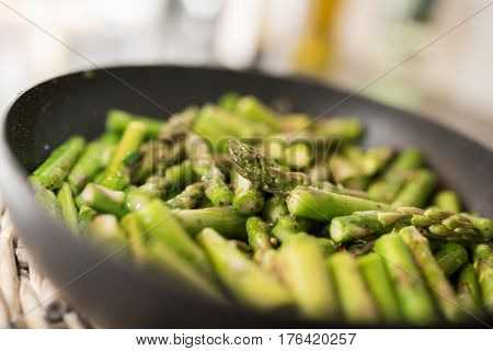 Fried green asparagus in a pan close up