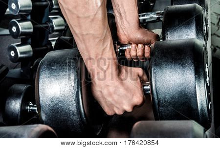 Close-up partial view of young man holding two dumbbells in gym