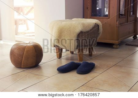 stool with fleece and slippers in living room by window