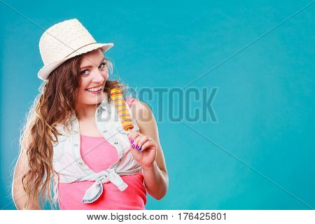Summer vacation happiness concept. Smiling joyful and cheerful woman fashionable female model eating popsicle ice pop on blue background