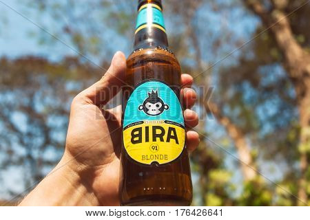 GOA, INDIA - FEB 28, 2017: Cold bottle of Indian craft blonde beer Bira 91 in a hand of drinker. Young company B9 Beverages owns Bira 91. 91 is international telephone code of India.