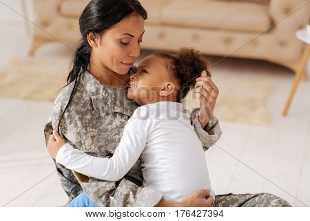 Protecting you from harm. Lively emotional adorable girl telling her mom about missing her while she serving abroad for several weeks