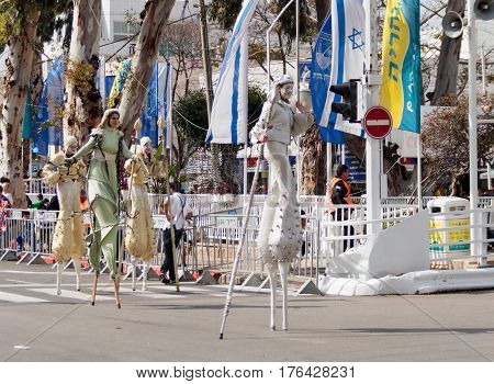 Participants At Carnival On Stilts Are Walking Along The Street