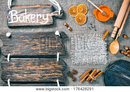 Dark wood boards as frames on burlap background with honey, nuts and aromatic spices. Wooden signboard with text 'Bakery' as title bar. Rustic style template for food and drink industry