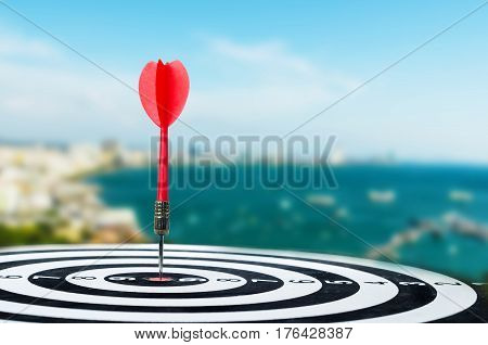 Close up shot red dart arrow on center of dartboard metaphor to target success winner concept on city and landscape blur background