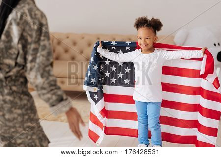 Look at me. Charismatic pretty young child meeting her mother at home while looking happy and being wrapped in a big flag