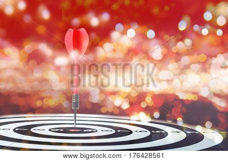 Close up shot red dart arrow on center of dartboard on bokeh blur background metaphor to target success winner concept