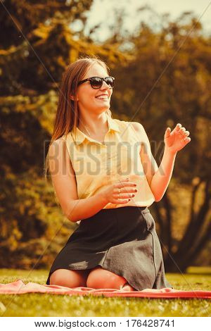Glamour fashion feminine concept. Cheerful girl kneeling in park. Young lady enjoying beautiful day outdoors.