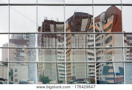 Distorted reflection of several multi-storied residential buildings in mirror surface of facing of shopping center opposite houses.