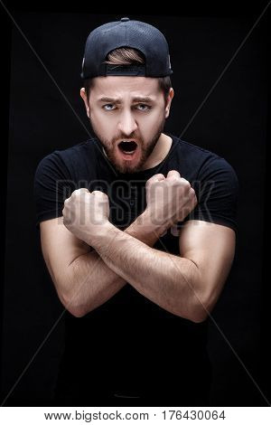 angry young man brunette in the black shirt and cap screaming on black background.