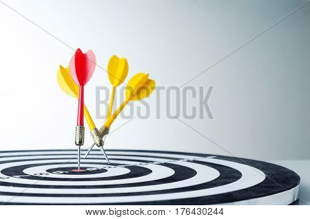 Close up shot red dart arrow on center of dartboard and yellow arrow not hit the target metaphor to target success winner and loser concept selective focus on red arrow