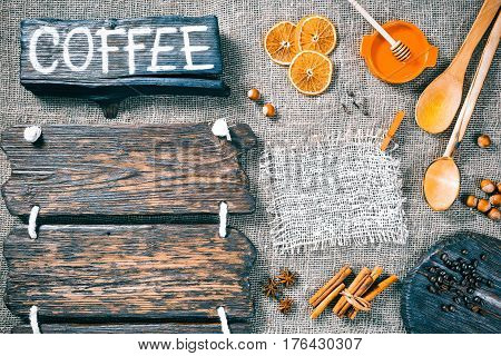 Dark wood boards as frames on burlap background with honey, nuts and aromatic spices. Wooden signboard with text 'Coffee' as title bar. Rustic style template for food and drink industry