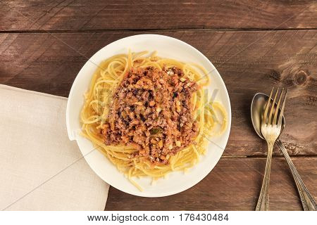 An overhead photo of a plate of pasta with meat and tomato sauce, with a place for text