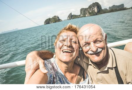 Happy retired senior couple taking travel selfie around world - Active elderly concept with people having fun together at Phang Nga bay Thailand - Mature people fun lifestyle - Retro contrast filter