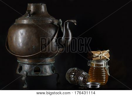 An ancient copper kettle on legs, a jar of honey and cinnamon sticks.