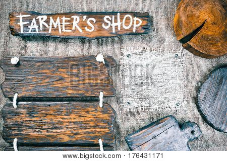 Dark wood boards, wood slice and burlap pieces as frames on burlap background. Wooden signboard with text 'Farmers shop' as title bar. Rustic style template for food and drink industry