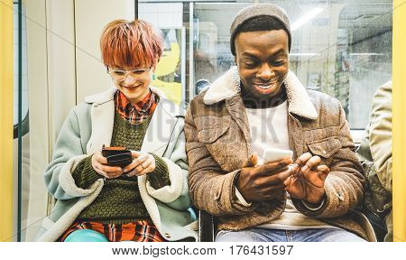 Multiracial hipster friends couple having fun with smartphone in subway train - Urban relationship concept with young people watching mobile phone in city underground area - Bright desaturated filter