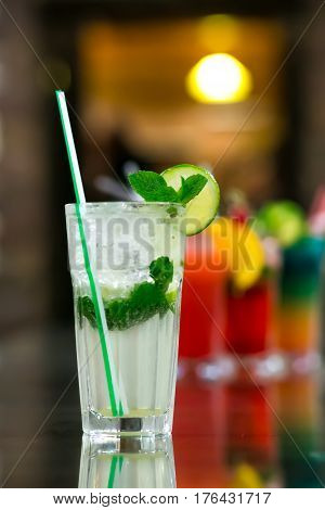 Two fresh mojitos cocktail on wooden background. Mojitos with mint leaves, lime and ice.