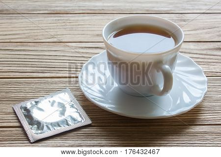 condom and a cup of coffee. coffee beans on old wooden table