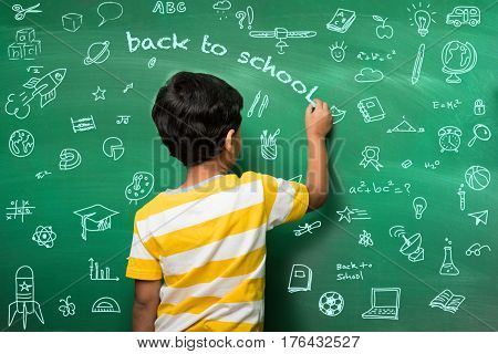 Indian school kid in hand stretched pose over green chalkboard or chalk board background, indian boy standing over green chalkboard background in the school with doodles -  back to school concept