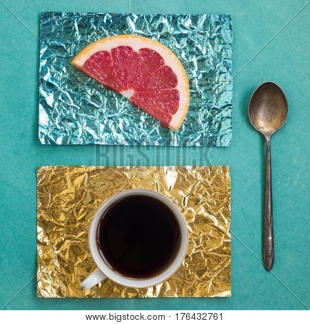 Orange slice and a cup of coffee on stands made of yellow and turquoise foil on a wooden surface