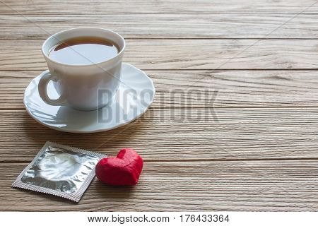 condom heart and a cup of coffee. coffee beans on old wooden table