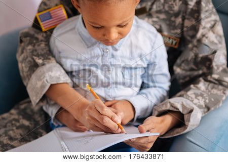 Pretty letters. Lively focused intelligent girl working on her handwriting using her mothers help while they spend their weekend together