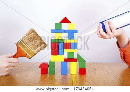 Boys repair the house from cubes by construction tools.Construction concept