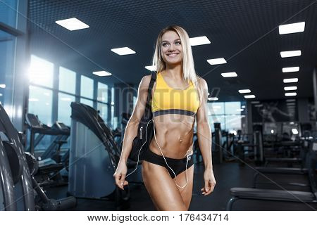 Sexy Athletic Sport Girl With Headphones Relaxing In The Gym